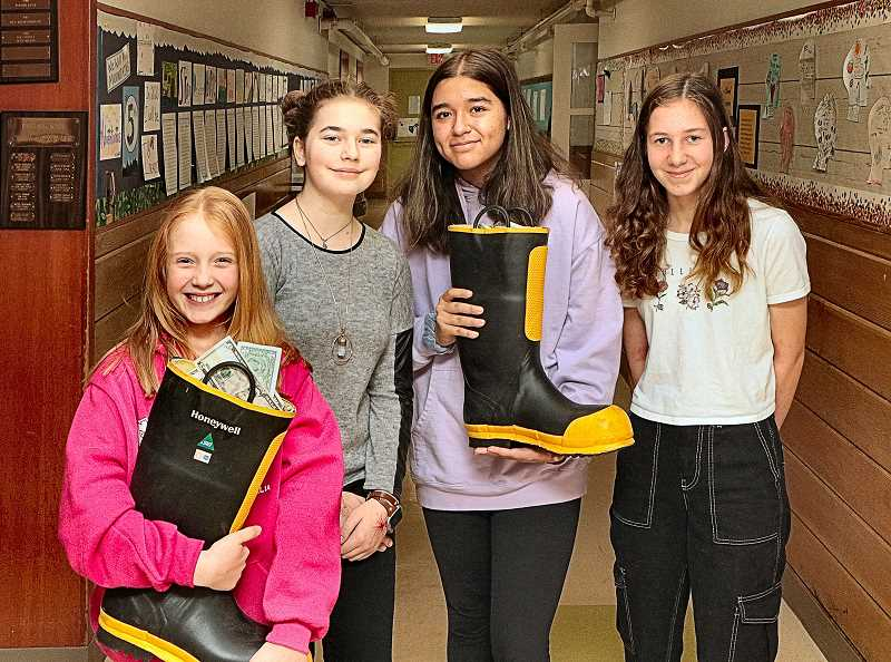 DAVID F. ASHTON - Holy Family Catholic School newcomer Georgia (left) holds one of the firefighter boots filled with donations destined to help those affected by the massive wildfires in her native Australia - here, accompanied by students Ava, Alejandra, and Brooke.