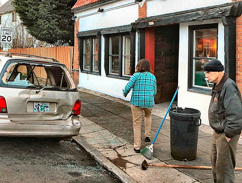 DAVID F. ASHTON - The owner of the parked car that was rear-ended, at far right, unhappily contemplates the damage, while a woman helps clean up the shattered glass. The broken gas pipes are visible just to the right of the car - and the gas meter is no longer there at all.