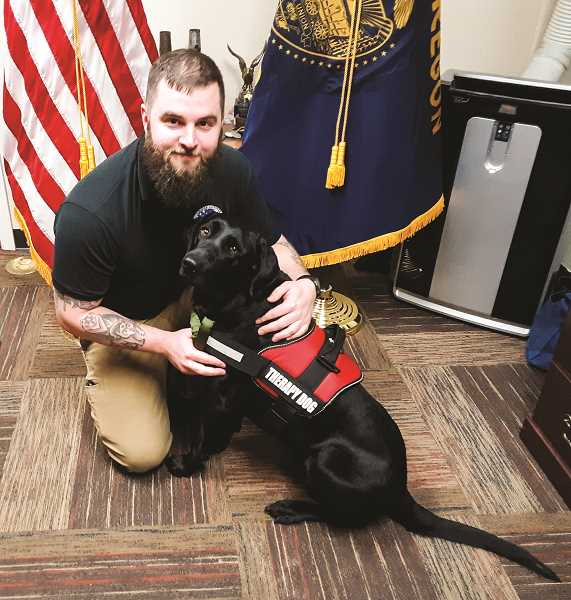 RAMONA MCCALLISTER - Erik Nelson and his therapy dog, Lily, pause for a photo at his office at Crook County Veteran's Services. Lily is 5 years old, and came on board last Thursday, Jan. 16.