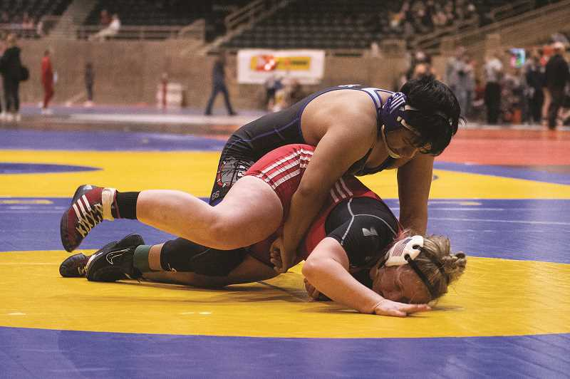 PMG PHOTO: LON AUSTIN - Woodburn's Alex Avendano picked up a 5-2 vicotry over Madras' Bailey Dennis to help the Bulldogs pull out a 37-24 win over the White Buffaloes in the opening match of the Oregon Wrestling Classic.