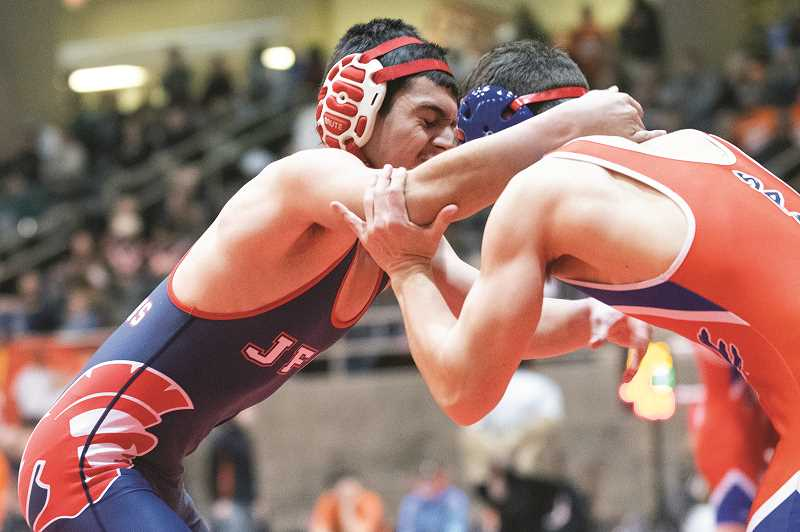 PMG PHOTO: LON AUSTIN - Kennedy's Daniel Beltran Reyes knots up with Pine Eagle's Cutter Tanaka in the opening seconds of the 132-pound match of the 2A/1A consolation semifinals on Saturday.