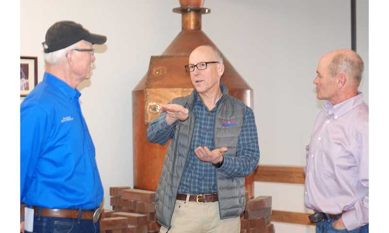 TERESA JACKSON/MADRAS PIONEER - Rep. Greg Walden, center, talks with Bruce Hoyt, left, and Rick Allen, right, in an unannounced visit to New Basin Distillery in Madras on Friday, Jan. 17. Walden and his wife, Mylene, talked with a handful of local men for about two hours during a lunch stop.