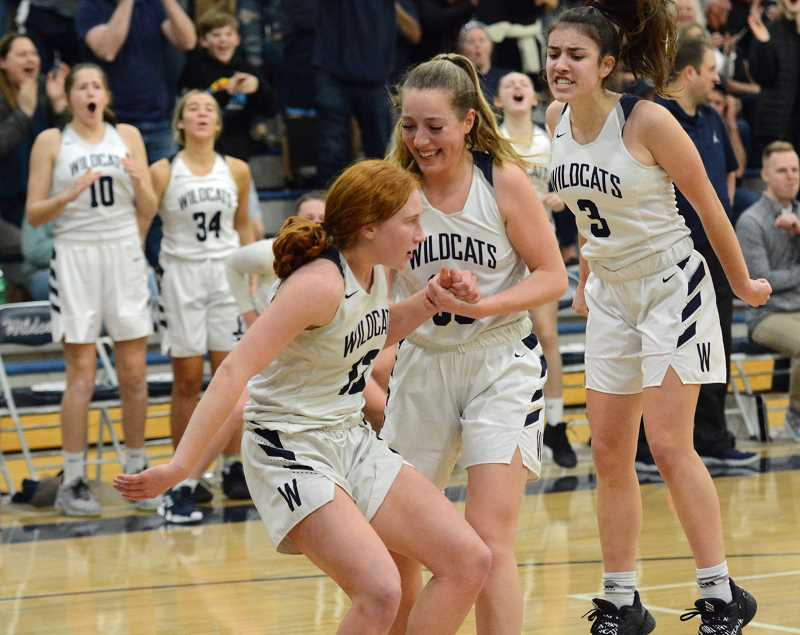 PMG PHOTO: DEREK WILEY - Wilsonville senior Kayla Hieb helps Sydney Burns up off the floor after Bruns scored and drew a foul in the fourth quarter of Tuesday's game against La Salle Prep.