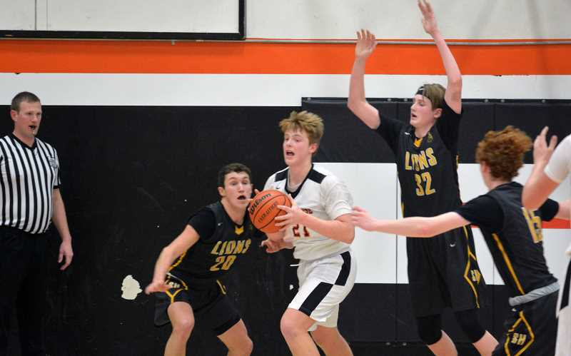 PMG PHOTO: MATT SINGLEDECKER - Scappoose post Luke McNabb looks for an open teammate against St. Helens last week.