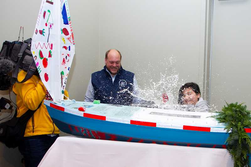 PHOTOS COURTESY OF COLUMBIA RIVER MARITIME MUSEUM - Columbia City Elementary School student Lili Garcia christens the student-made mini boat, coined 'Philbert,' with Martinellis sparkling cider as Nate Sandel, education director for the Columbia River Maritime Museum, reacts.