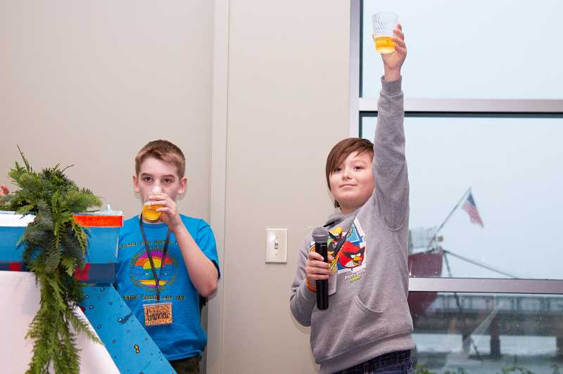 PHOTO COURTESY COLUMBIA RIVER MARITIME MUSEUM - Darren Bjornstrom, right, raises a toast while classmate Gunnar Kester takes a sip of apple cider during the christening and launch ceremony for Columbia City Elementary School's mini boat held in Astoria on Thanksgiving Day.
