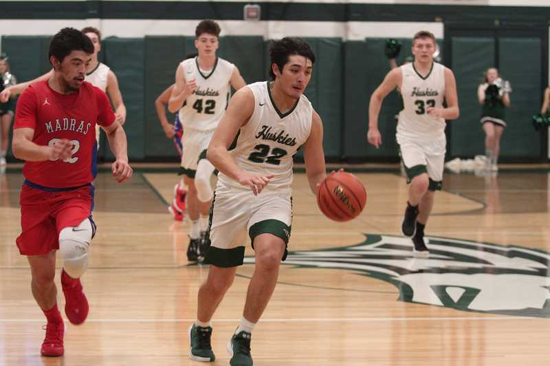 PMG PHOTO: PHIL HAWKINS - North Marion senior Sergio Jimenez leads the fast break in transition as the Huskies seek to increase their lead in the 83-52 victory over the Madras White Buffaloes on Friday. Jimenez scored 10 points as one of five North Marion players to reach double digits on offense.