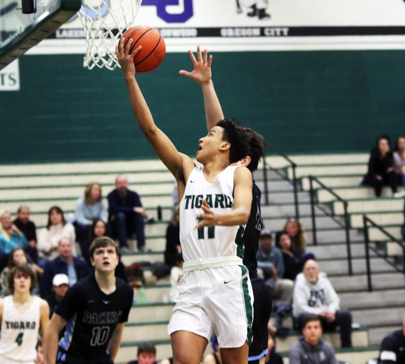 PMG PHOTO: DAN BROOD - Tigard High School freshman Kalim Brown goes up to the basket for a layup in the opening moments of the Tigers' 72-51 win over Lakeridge on Friday.