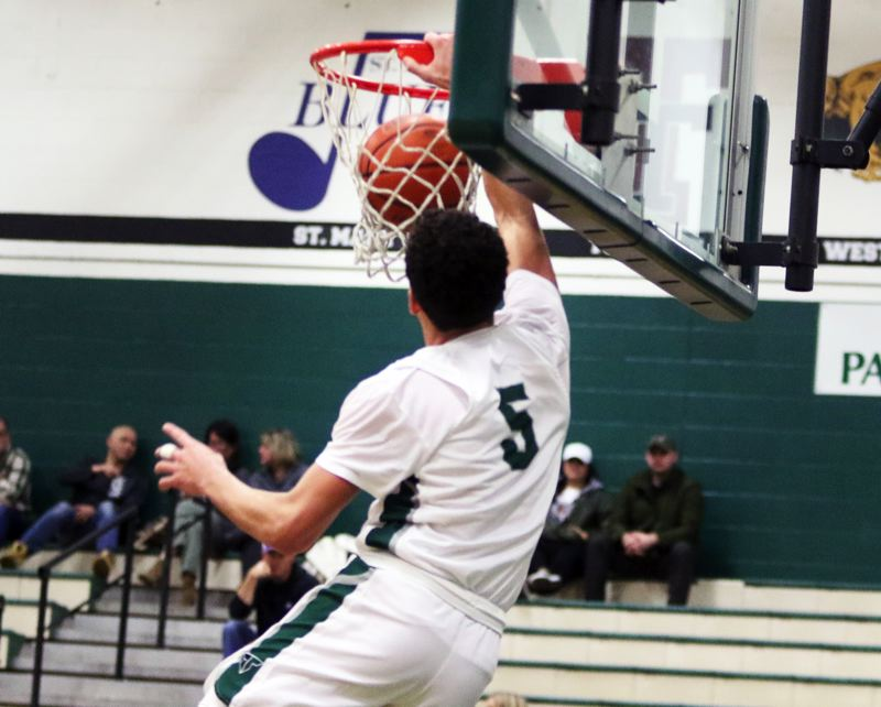 PMG PHOTO: DAN BROOD - Tigard High School junior Drew Carter throws down a one-handed dunk, coming off an alley-oop pass from junior Edward Beglaryan, during the Tigers' 72-51 win over Lakeridge on Friday.