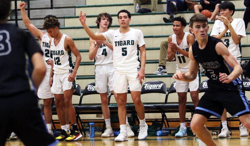 PMG PHOTO: DAN BROOD - The Tigers celebrate a late basket during their 72-51 Three Rivers League victory over Lakeridge on Friday.