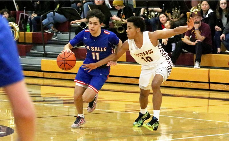 PMG PHOTO: JIM BESEDA - La Salle Prep's Nic Boyd (11) runs into defensive resistance from Milwaukie's Alileyon Ford (10) during the second half of Friday's Northwest Oregon Conference boys basketball game