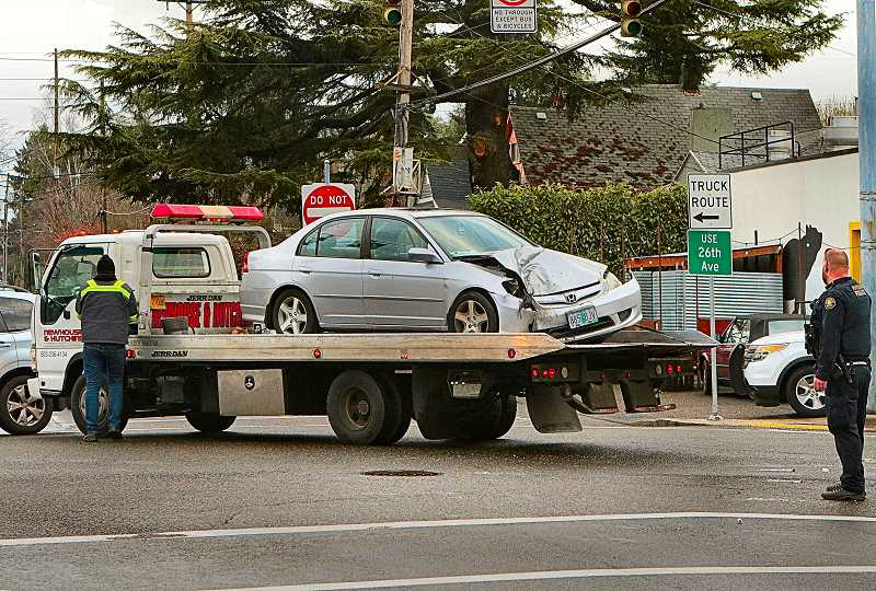 DAVID F. ASHTON - A tow truck responded to clear the smashed car from the S.E. 28th and Holgate intersection, and get the morning commute traffic moving again.