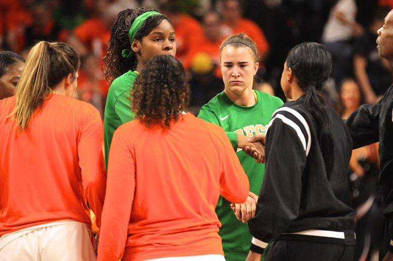 PMG PHOTO: JAIME VALDEZ - Oregon and Oregon State players greet before the jump to start their game and in the wake of news that basketball legend Kobe Bryant has died in a helicopter crash.