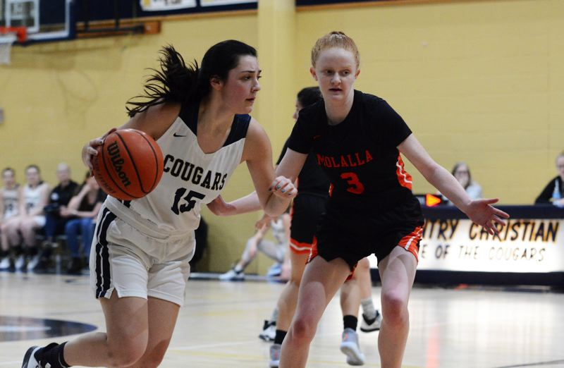 PMG PHOTO: DEREK WILEY - Annie Bafford dribbles the ball at Hannah Nelzen Saturday at Country Christian.