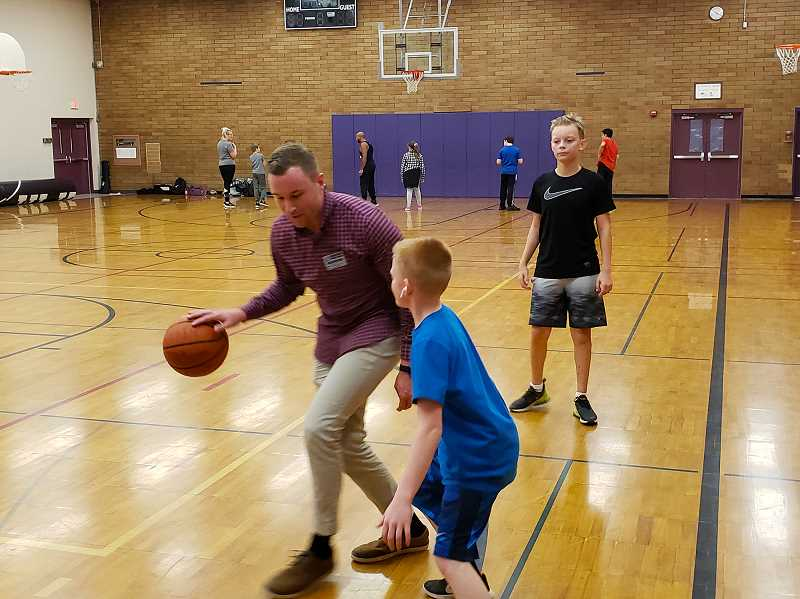 COURTESY PHOTO - Kraxberger students Cody McMurtrie and Rylan Fisher play pickup basketball with Miles Brandon of Northwest Family Services during the KAOS after-school program.