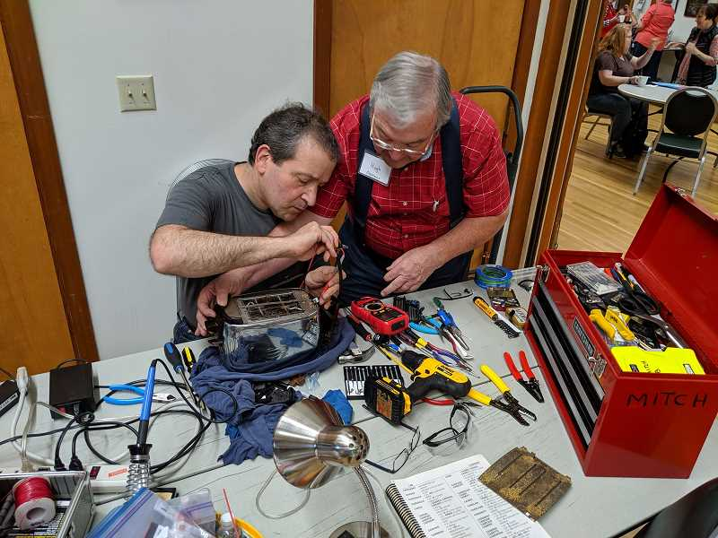PMG FILE PHOTO - Mitch Bayersdorfer (left) and Hugh Hudson (right) work to repair a toaster at a former Lake Oswego Repair Fair.