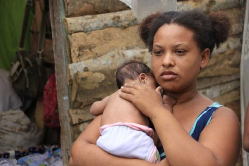 COURTESY PHOTO: SARAH RAWLINS - Stefanie, a Venezuelan migrant living in Colombia, holds her 6-month-old baby outside of her makeshift home near Barranquilla. Medical Teams International hopes to help migrants like Stefanie with a new grant.