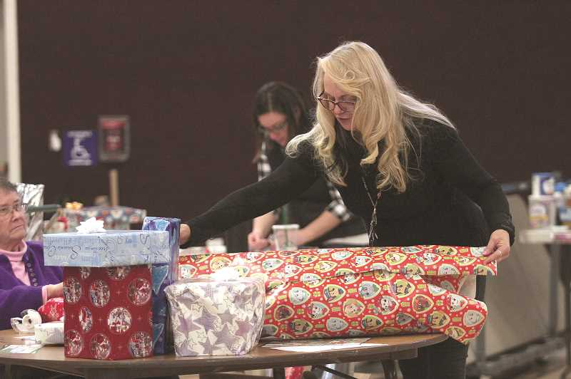 PMG FILE PHOTO - Volunteers for Love Santa, Inc. spend countless hours each year gathering, wrapping and distributing Christmas presents to families in northern Marion County.