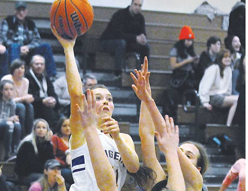 GRAPHIC PHOTO: GARY ALLEN - Junior guard Ashley Kosmicki drives through a pair of defenders in Newberg's 44-37 loss to Sherwood on Friday.