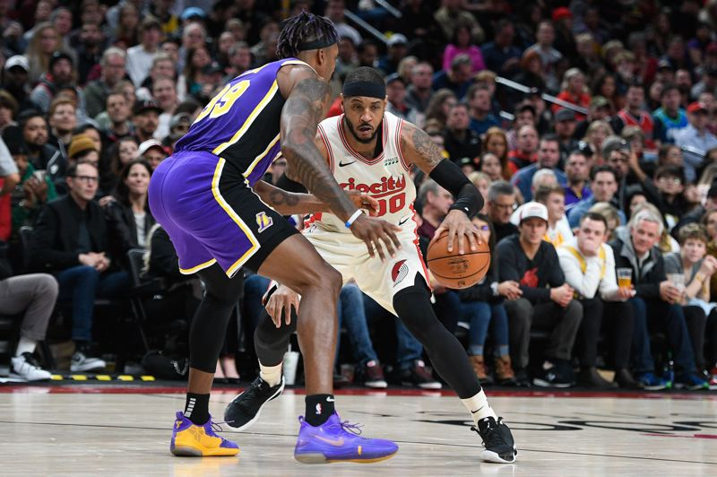 PMG PHOTO: CHRISTOPHER OERTELL - Trail Blazers forward Carmelo Anthony works the dribble against Dwight Howard of the Los Angeles Lakers.