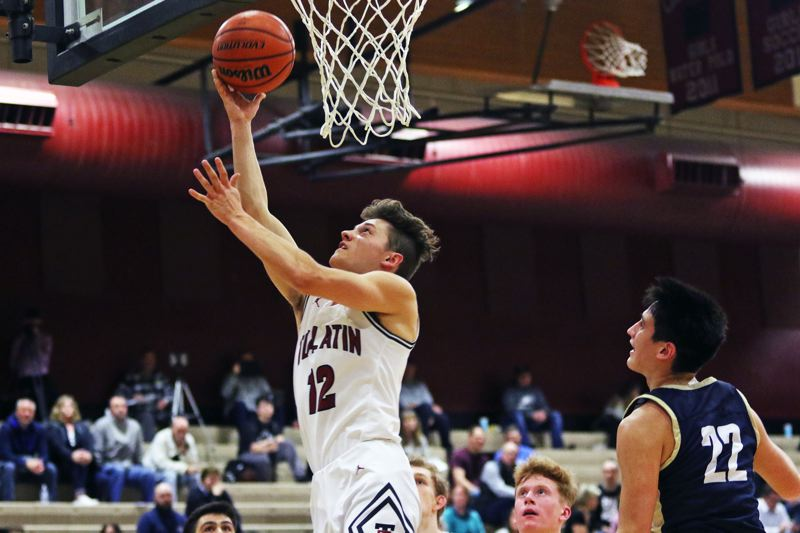PMG PHOTO: DAN BROOD - Tualatin High School senior Sam Noland (12) goes up to the basket during the Timberwolves' 58-47 victory over Canby in Tuesday's Three Rivers League game.