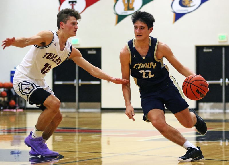 PMG PHOTO: DAN BROOD - Canby High School junior Diego Arredondo (22) tries to drive past Tualatin senior Sam Noland during Tuesday's Three Rivers League game. The Wolves won 58-47.