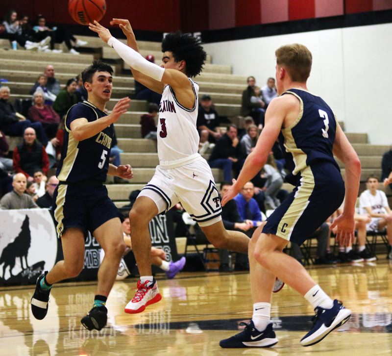 PMG PHOTO: DAN BROOD - Tualatin High School sophomore Noah Ogoli (3) throws a pass on the run during the Timberwolves' 58-47 win over Canby in Tuesday's Three Rivers League game.