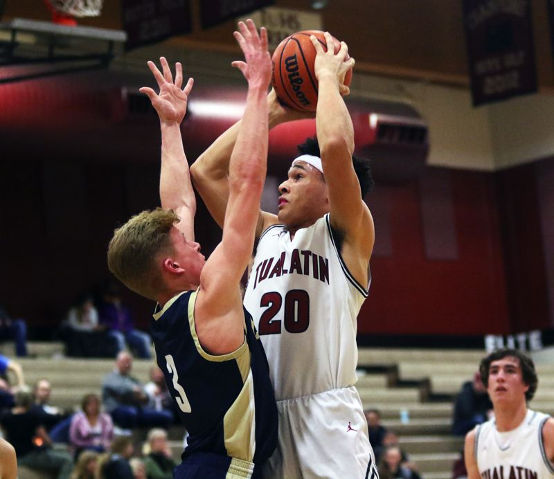 PMG PHOTO: DAN BROOD - Tualatin High School senior John Miller (20) looks to shoot over Canby junior Tyler Mead during Tuesday's Three Rivers League contest. The Wolves got a 58-47 win.
