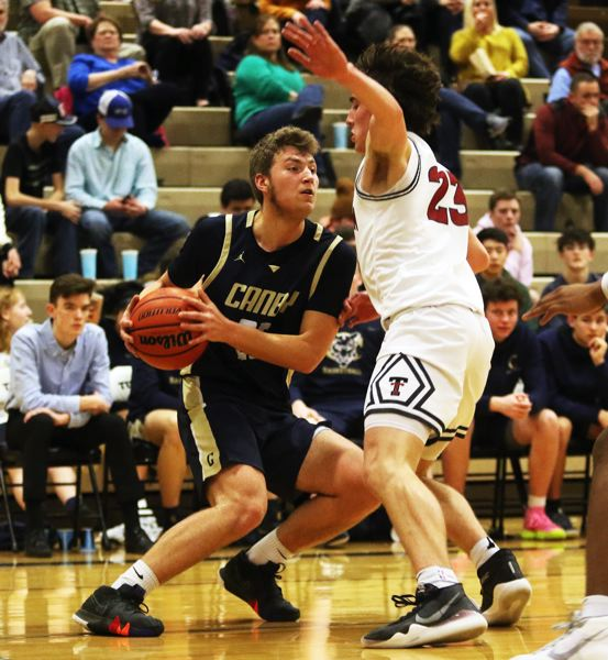 PMG PHOTO: DAN BROOD - Canby High School junior Aftanom Ovchinnikoff (left) tries to get past Tualatin sophomore Peter Burke during Tuesday's Three Rivers League contest.