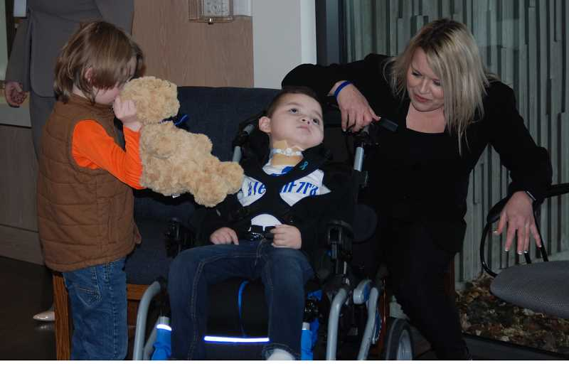 TERESA JACKSON/MADRAS PIONEER - Little Roy Fast, 7, gives a teddy bear to Ezra Thomas, 4, as Ezra's grandmother Tina Jorgensen looks on. Both boys received permanent injuries at the hands of their abusers. Their caregivers want to see longer sentences for abusers in future cases.