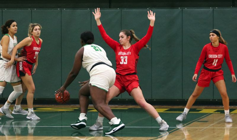 PMG PHOTO: JIM BESEDA - Oregon City's Emmaly Welch (33) stands her ground as West Linn's Aaronette Vonleh (21) drives the lane during the first half of Tuesday's Three Rivers League girls basketball game at West Linn.