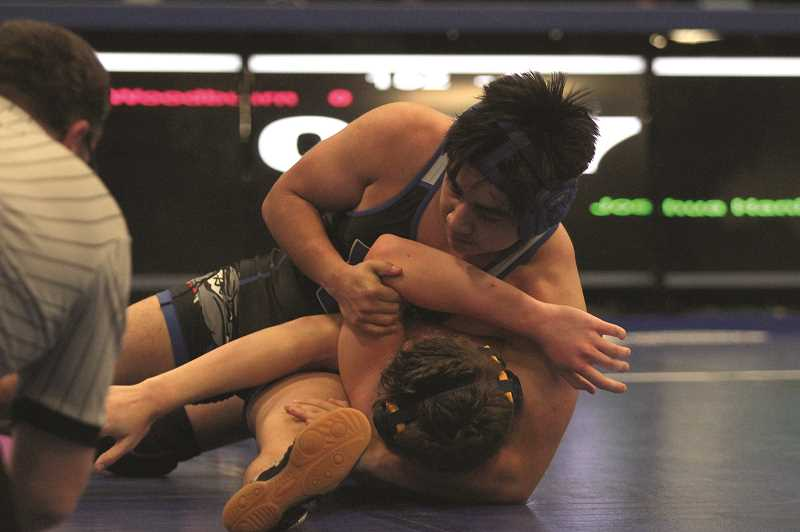 PMG PHOTO: PHIL HAWKINS - Woodburn's Misael Ramos scored a 21-6 technical fall over Banks' Joshua Hanlon at the end of the second period in the Bulldogs' home 3-way against the Braves and the defending state champion Tillamook Cheesemakers.