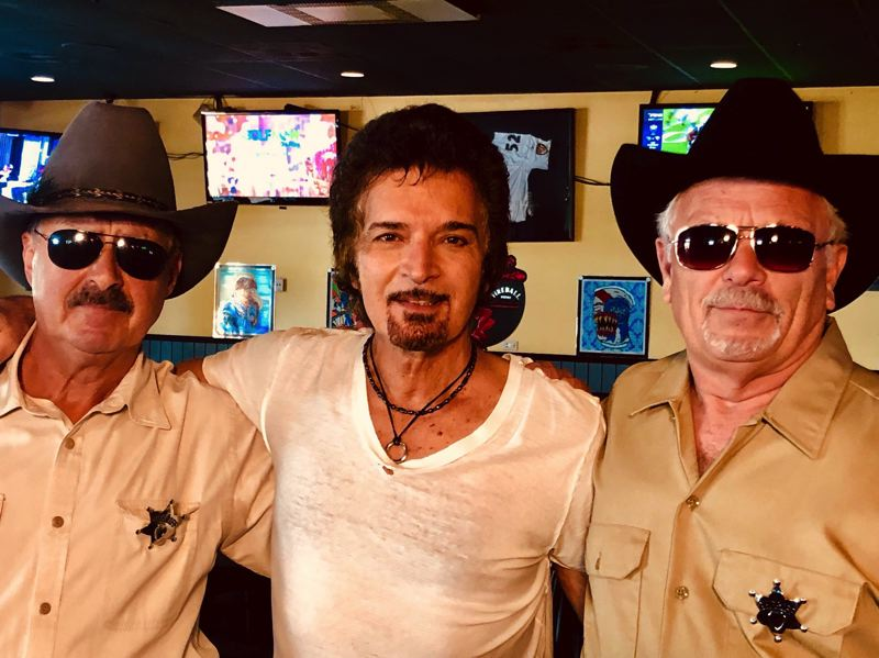 COURTESY PHOTO: GINO VANNELLI  - Gino Vannelli, center, invited Troutdale Realtor Ken Cahill, left, and Troutdale General Store owner Terry Smoke to play sheriffs deputies in the video for Older N Wizer, shot at Troutdales Skyland Pub in 2019.