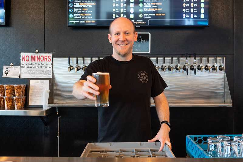 PMG PHOTO: CHRISTOPHER OERTELL - Neal Glaske holds a glass of beer behind the counter at the Noble Hop Bierhouse in Hillsboro. It also offers wine and nonalcoholic beverages like kombucha and CBD drinks.