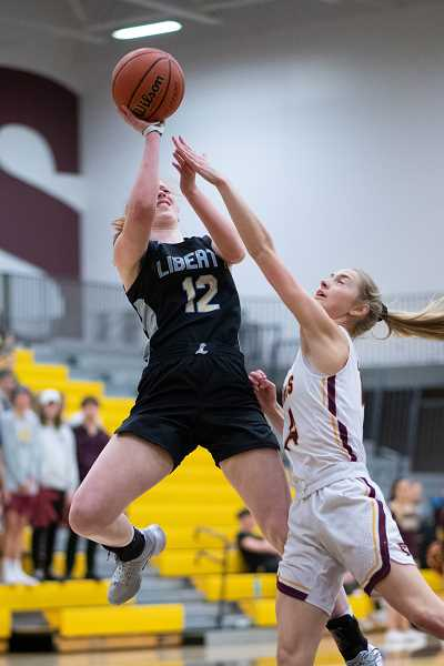 PMG PHOTO: CHRISTOPHER OERTELL - Liberty's Breeze Bartle (12) and Forest Grove's Ally Hammond (14) during a girls basketball game at Forest Grove High School in Forest Grove, Ore., on Friday, Jan. 31, 2020.