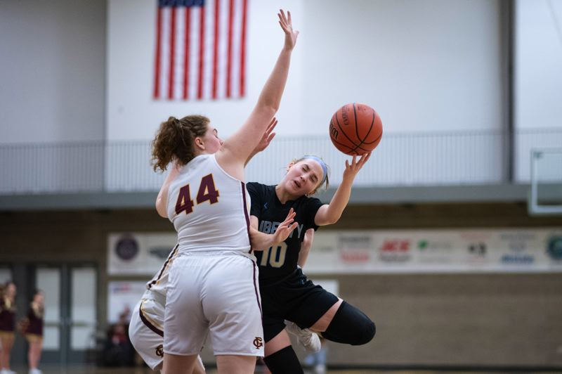 PMG PHOTO: CHRIS OERTELL - Liberty's Livia Knapp (right) gets fouled by Forest Grove's Olivia Grosse during the Falcons' 67-35 win at Forest Grove High School on Friday, Jan. 31.