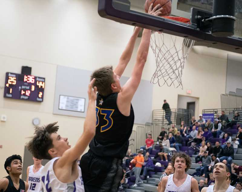 LON AUSTIN/CENTRAL OREGONIAN - Cayden Lowenbach goes up for a dunk over a trio of Ridgeview defenders. Lowenbach had a pair of dunks in the contest and finished with 12 points as the Cowboys rolled past the Ridgeview Ravens.