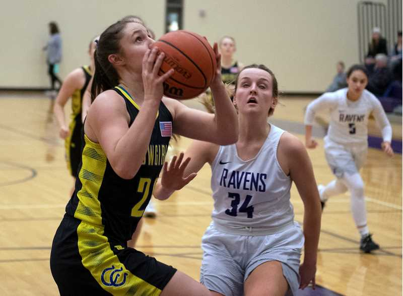LON AUSTIN/CENTRAL OREGONIAN - Liz Barker goes to the basket for two of her team high 17 points Friday night against the Ridgeview Ravens. Barker also had nine rebounds in the game, but it wasn't enough as the Ravens took a 65-38 home-court victory over the Cowgirls.