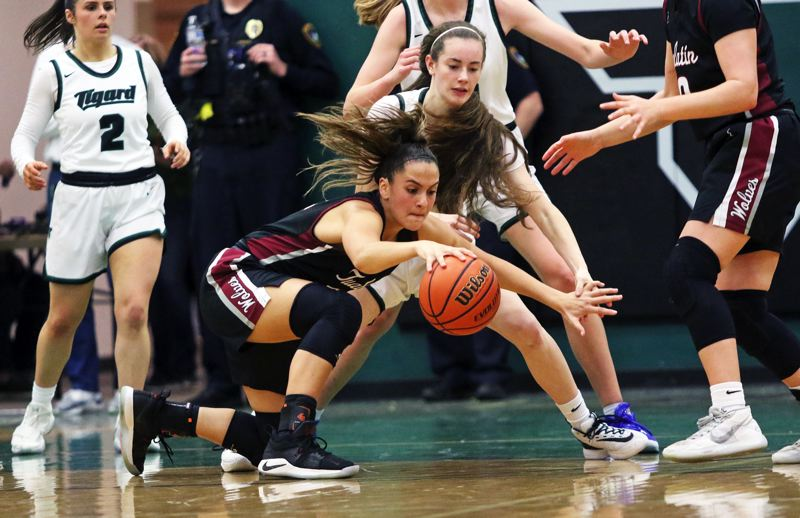 PMG PHOTO: DAN BROOD - Tualatin High School junior Sidney Dering goes for a loose ball in front of Tigard freshman Karen Spadafora during Friday's Three Rivers League game. The Wolves won 39-34.
