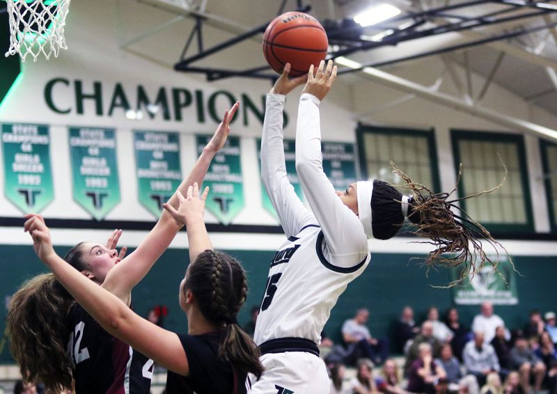 PMG PHOTO: DAN BROOD - Tigard High School junior Ajae Holdman (right) takes a jump shot during the Tigers' Three Rivers League game with Tualatin on Friday.