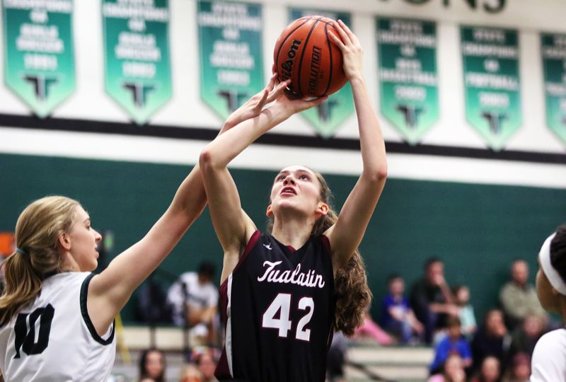PMG PHOTO: DAN BROOD - Tualatin High School junior Natalie Lathrop (right) looks to take a shot against Tigard sophomore Sarah Lamet during Friday's Three Rivers League contest.