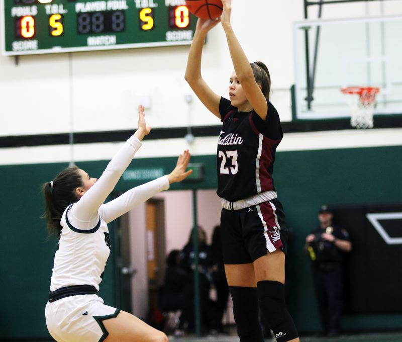 PMG PHOTO: DAN BROOD - Tualatin High School freshman Tabi Searle (right) looks to throw a pass over Tigard senior Kennedy Brown during Friday's Three Rivers League contest at Tigard.