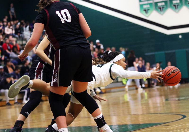 PMG PHOTO: DAN BROOD - Tigard High School junior Ajae Holdman dives for a loose ball during the Tigers' Three Rivers League game with Tualatin on Friday.