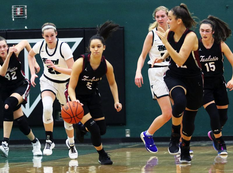 PMG PHOTO: DAN BROOD - Tualatin High School senior Sophie Bennett (5) looks the get the ball upcourt on a fast break during the Wolves' 39-34 win at Tigard on Friday.