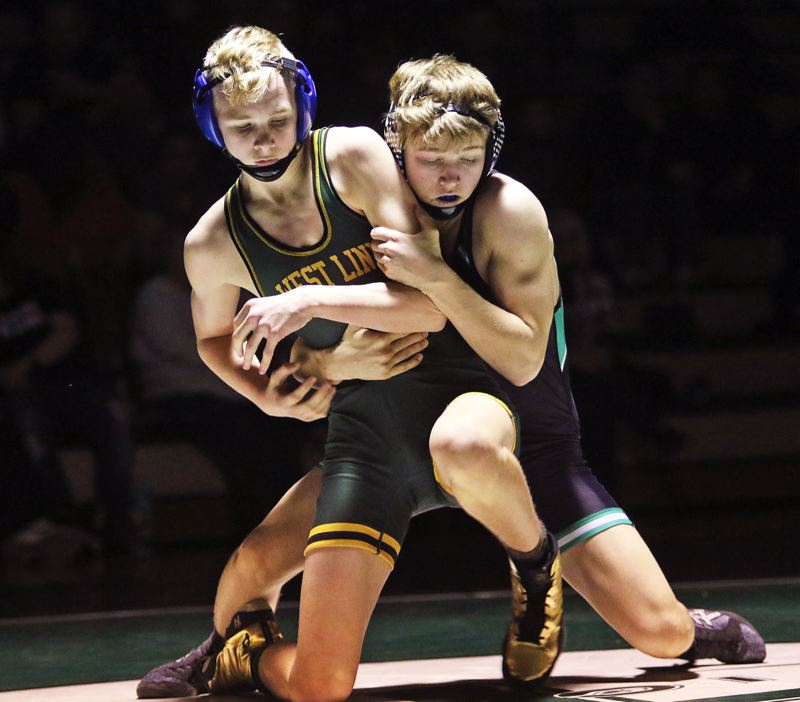 PMG PHOTO: DAN BROOD - West Linn's Logan Owens (left) battles Tigard's Chase Dennis during Owens' 3-2 decision at 132 pounds in the Lions' 61-11 victory at Tigard High School on Thursday, Jan. 30.