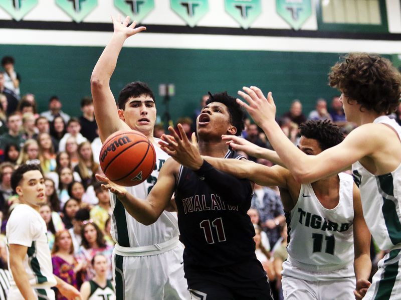 PMG PHOTO: DAN BROOD - Tualatin High School sophomore Malik Ross (center) looks to get to the basket between Tigard's Edward Beglaryan and Kalim Brown during Friday's game. Ross scored 12 points in the Wolves' 60-45 win.