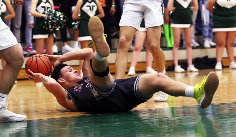 PMG PHOTO: DAN BROOD - Tualatin High School senior John Miller has the ball as he's on the court during Friday's rivalry game at Tigard. Miller scored 19 points for the Wolves in their 60-45 win.