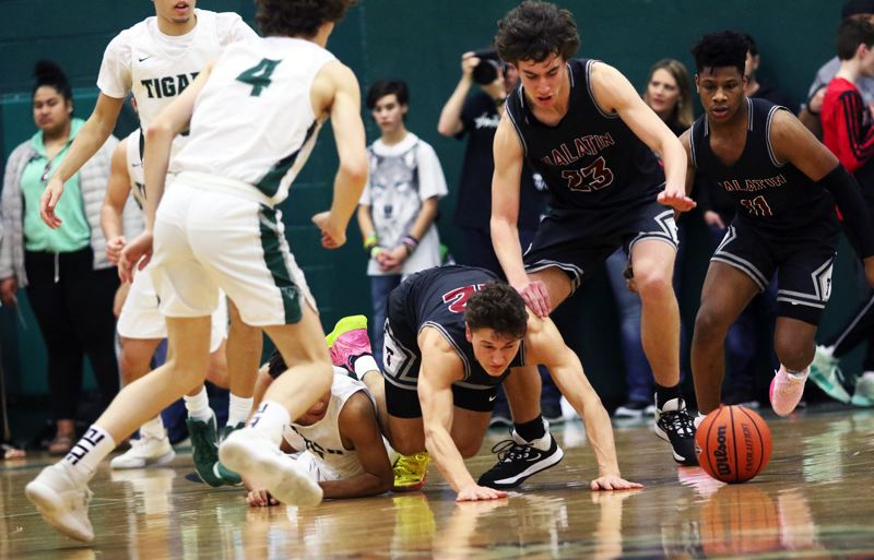 PMG PHOTO: DAN BROOD - Tigard High School senior Brett Moss (4) and Tualatin's (from left) Sam Noland, Peter Burke and Malik Ross all look to grab a loose ball during Friday's Three Rivers League game.