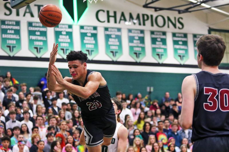 PMG PHOTO: DAN BROOD - Tualatin High School senior John Miller (20) is fouled as he puts up a shot during the Timberwolves' 60-45 win at Tigard on Friday.