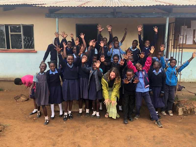 Ryen Parno joins her middle school students in Zambia, Africa, for a group photo outside of their school.